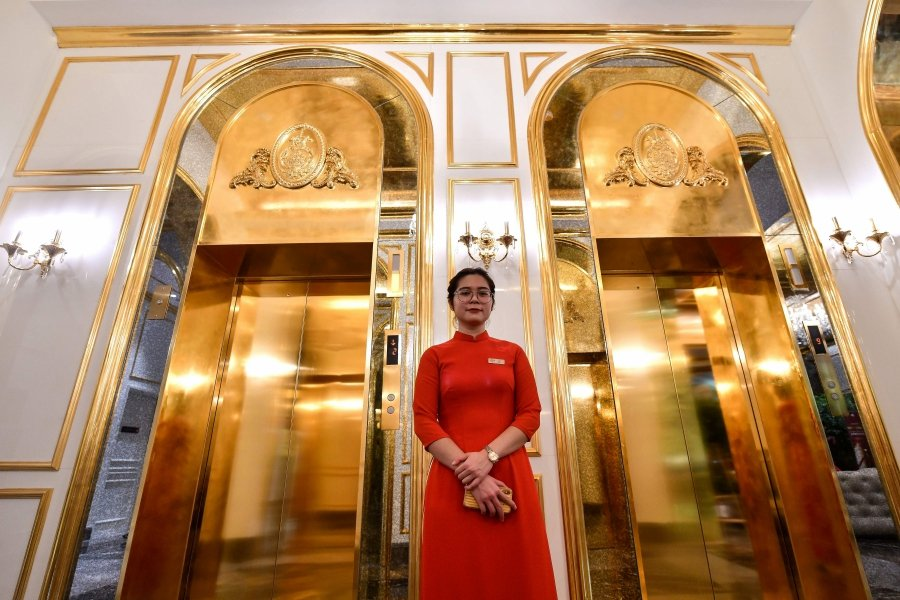A staff member stands near the lifts in the lobby of the newly-inaugurated Dolce Hanoi Golden Lake hotel, the world's first gold-plated hotel, in Hanoi. (Photo by Manan VATSYAYANA / AFP)