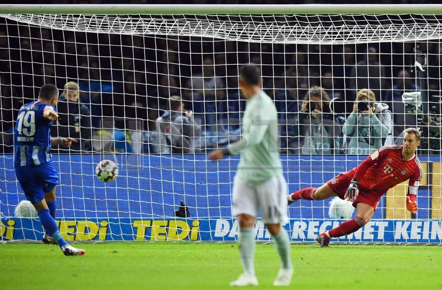 Hertha Berlin's Vedad Ibisevic (left) scores the 1-0 lead from the penalty spot against Bayern Munich's goalkeeper Manuel Neuer (right) during the German Bundesliga match in Berlin. -EPA