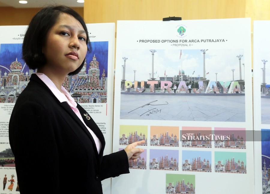 Wan Jamila Wan Shaiful Bahri shows the selected artwork. -NSTP/Mohd Fadli Hamzah