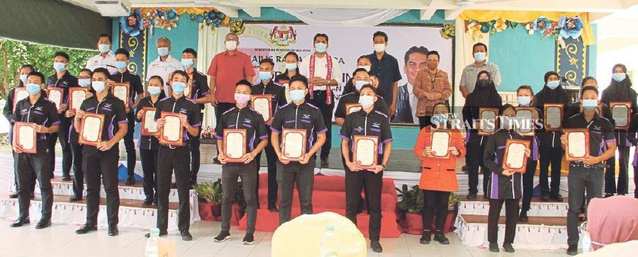 Senior Education Minister Dr Radzi Jidin (top row, centre) with members of the teaching community at a ceremony held at SMK Kudat II.