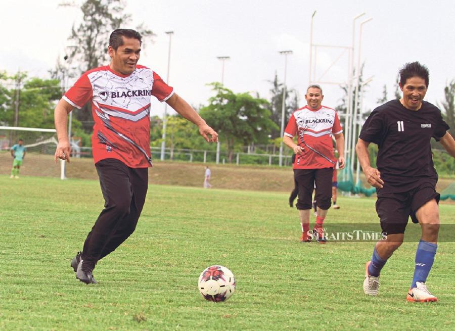 Dr Radzi Jidin (left) joined the local community in a friendly football match at the Kudat Sports Complex. PIX BY MALAI ROSMAH TUAH