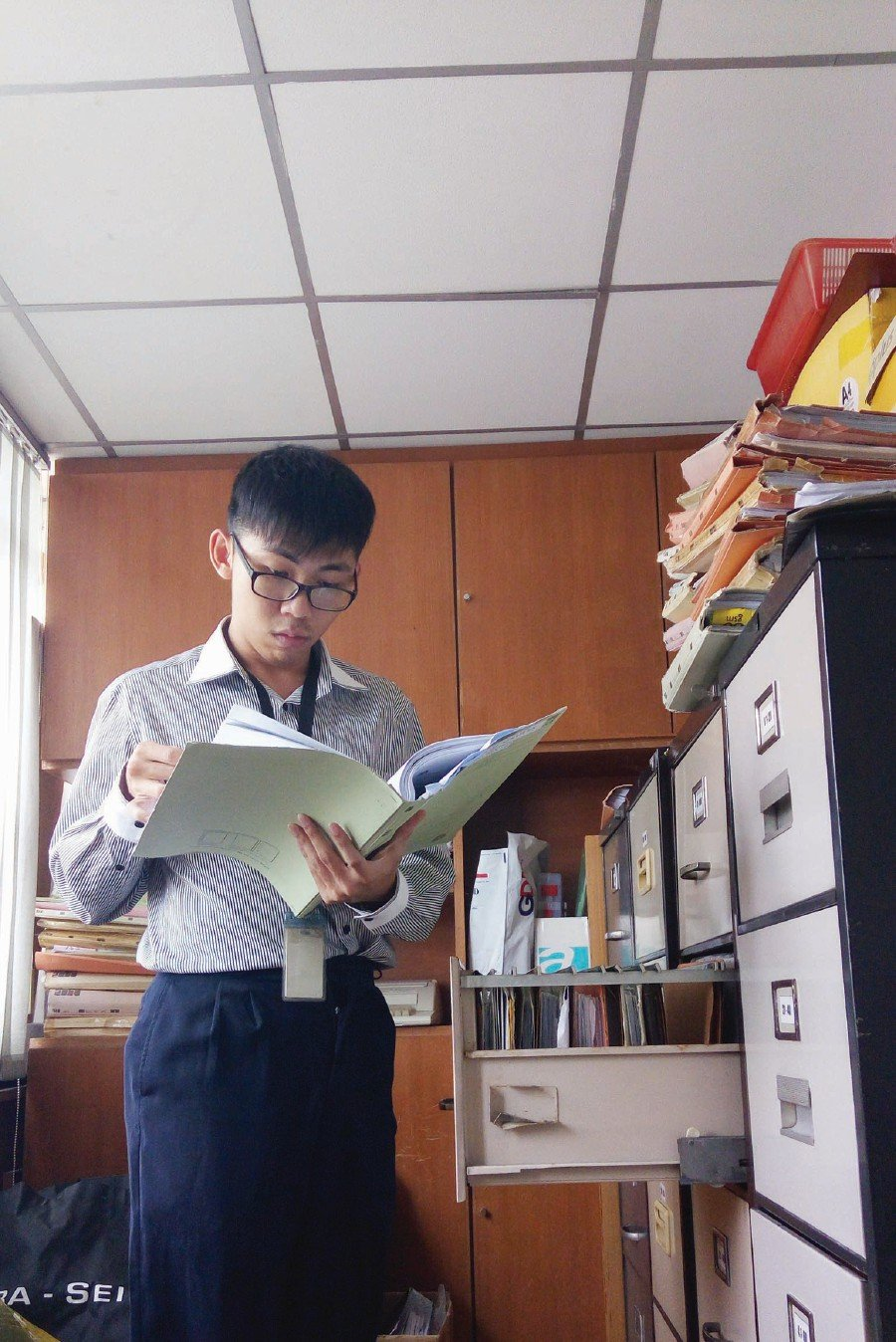 Young Teng Wai busy at work in an accounting firm.