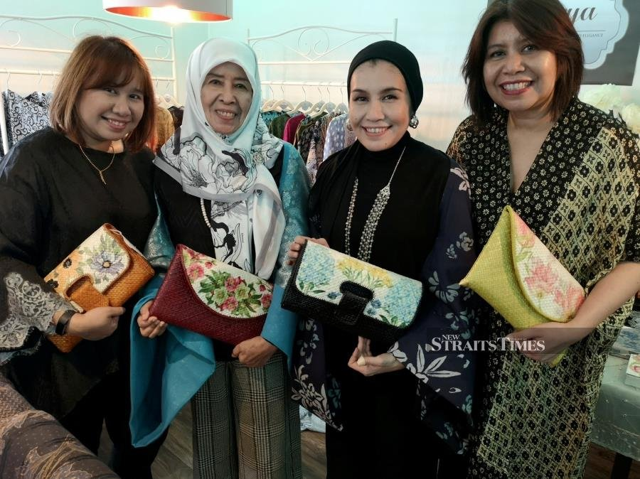 Hajah Rosmaniar with her daughters, wearing clothes from Qarya collection and holding clutches from House of Chinta. PIC BY ZAHARAH OTHMAN