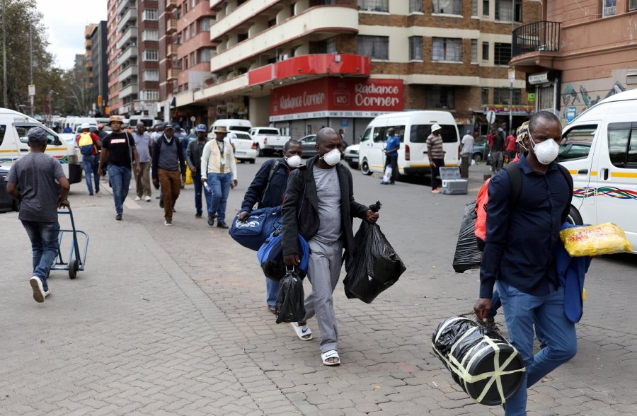 Passengers wearing masks walk to a taxi rank as residents of a number of African cities where the coronavirus is spreading are heading to the countryside to try to escape from the disease, in Johannesburg, South Africa, March 25, 2020. REUTERS/Siphiwe Sibeko