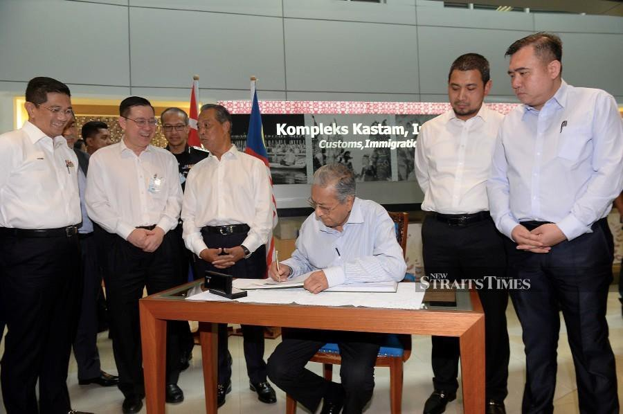 Prime Minister Tun Dr Mahathir Mohamad signing a guest book during the Continuation Rapid Transit System (RTS) Link between Johor Bharu and Singapore Announcement Press Conference at the Bangunan Sultan Iskandar (BSI) Customs, Immigration and Quarantine (CIQ) Complex today. (BERNAMA)