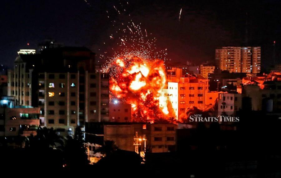 An explosion is pictured among buildings during an Israeli airstike on Gaza City. - AFP