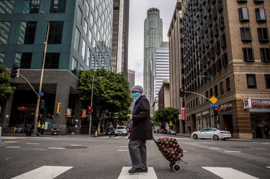 A woman wearing a mask walks in Downtown Los Angeles during the coronavirus (COVID-19) outbreak. - AFP pic