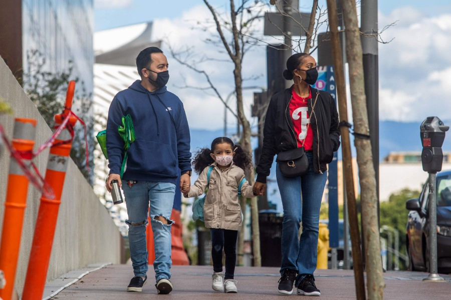 A family walks wearing masks in Downtown Los Angeles during the coronavirus (COVID-19) outbreak. - AFP pic