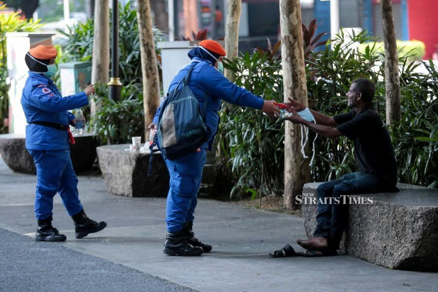 A Civil Defence Force personnel handing out water and face mask to a man in Kuala Lumpur. - NSTP/ASYRAF HAMZAH