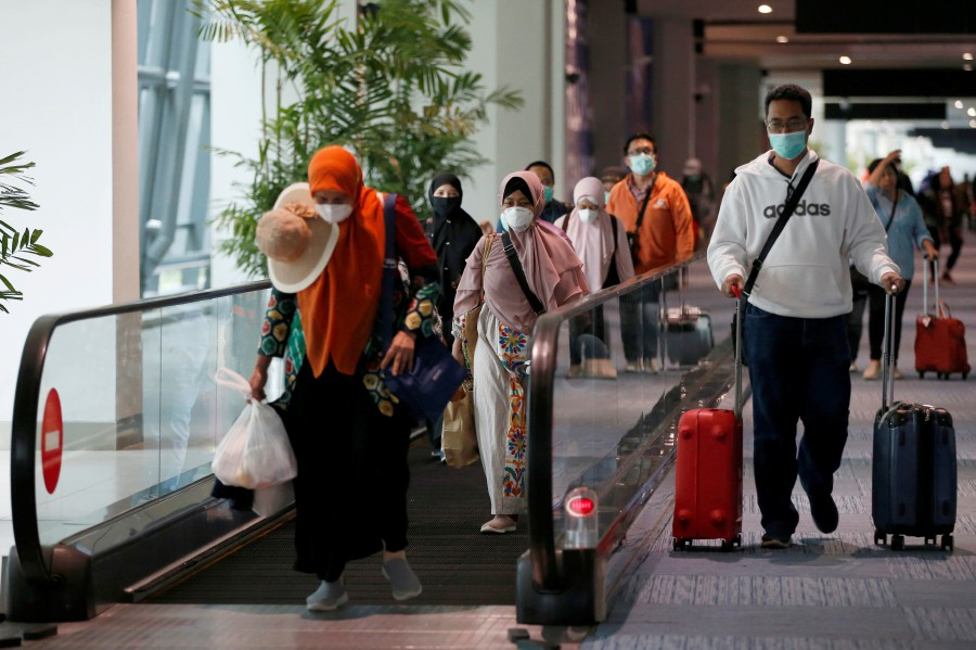 Passengers wearing face masks walk as they arrive at international terminal of Soekarno-Hatta Airport near Jakarta, amid the coronavirus disease (COVID-19), Indonesia. -REUTERS pic
