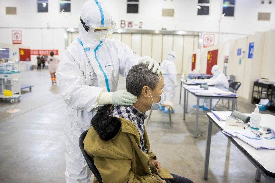 A member of the medical staff (left) massaging a patient an exhibition centre converted into a hospital in Wuhan in China's central Hubei province. -AFP
