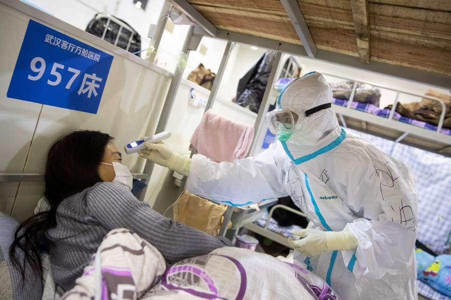 A medical staff (right) checking the body temperature of a patient at an exhibition centre converted into a hospital in Wuhan in China's central Hubei province. - AFP
