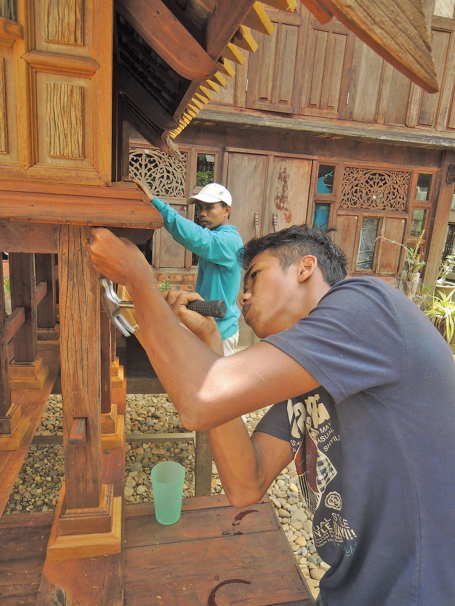 Workers busy building a traditional Malay house replica.