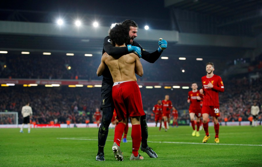 Liverpool's Mohamed Salah celebrates scoring their second goal with Alisson. -Reuters