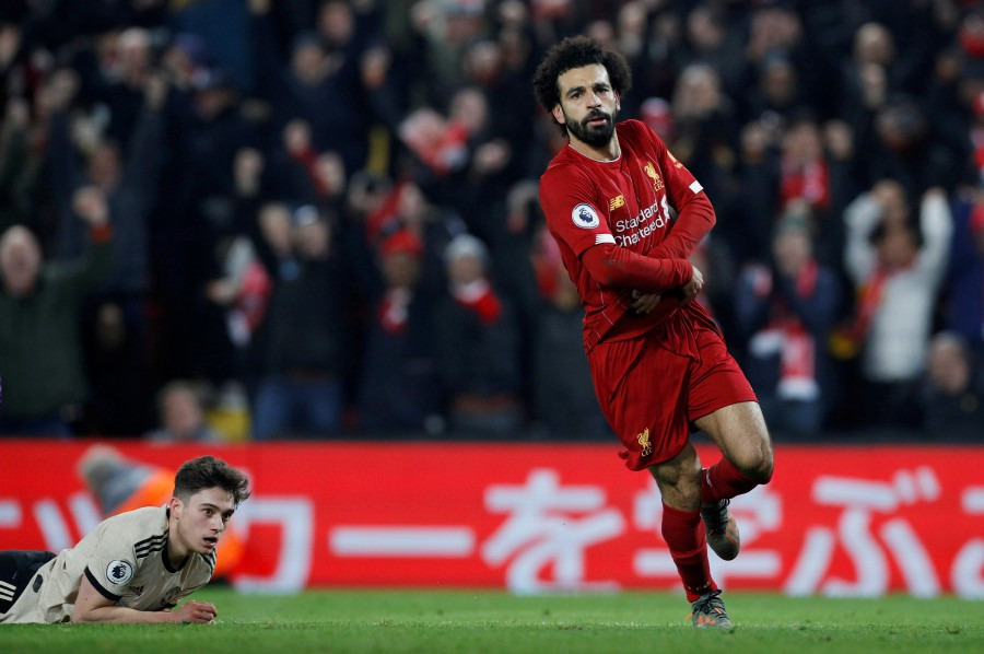 Liverpool's Mohamed Salah takes his shirt off when celebrating scoring their second goal. -Reuters