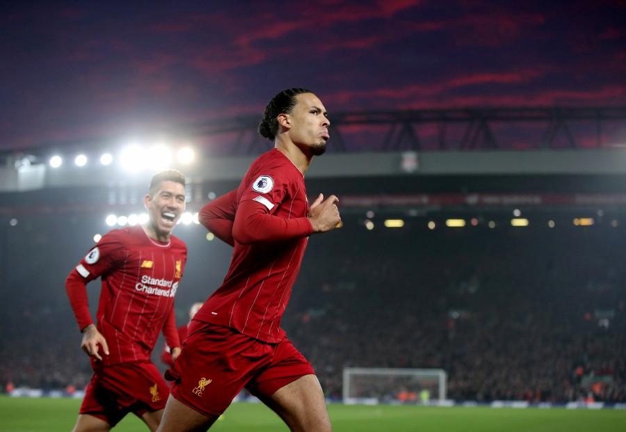 Liverpool's Virgil van Dijk celebrates scoring their first goal with Roberto Firmino. -Reuters