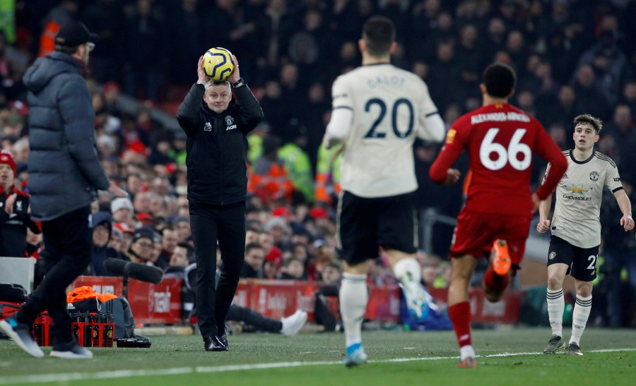 Manchester United manager Ole Gunnar Solskjaer throws the ball. -Reuters