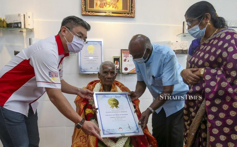 Malaysia Book of Records (MBOR) chief executive officer Christopher Wong (left) presents a framed certificated to  A. Annamahm while being helped by her son M. Subramanian. -NSTP/DANIAL SAAD
