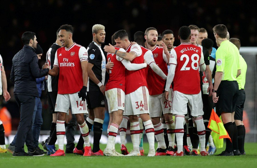 Arsenal manager Mikel Arteta shakes hands with Pierre-Emerick Aubameyang as Granit Xhaka celebrates with Hector Bellerin after the match. -Reuters
