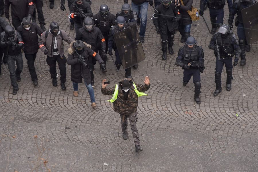 """A man wearing a yellow vest raises his hands as anti-riot policemen stand on the Champs Elysees in Paris during a """"yellow vest"""" (gilet jaune) protest against rising costs of living they blame on high taxes, on December 8, 2018. - Paris was on high alert on December 8 with major security measures in place ahead of fresh """"yellow vest"""" protests which authorities fear could turn violent for a second weekend in a row. (Photo by Lucas BARIOULET / AFP)"""