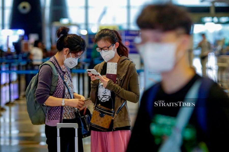 This March 7 pic shows passengers wearing face masks at Kuala Lumpur International Airport. -NSTP/AIZUDDIN SAAD