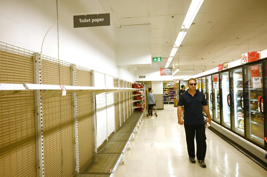 Shelves are empty of toilet rolls in a supermarket in Sydney. - AFP pic