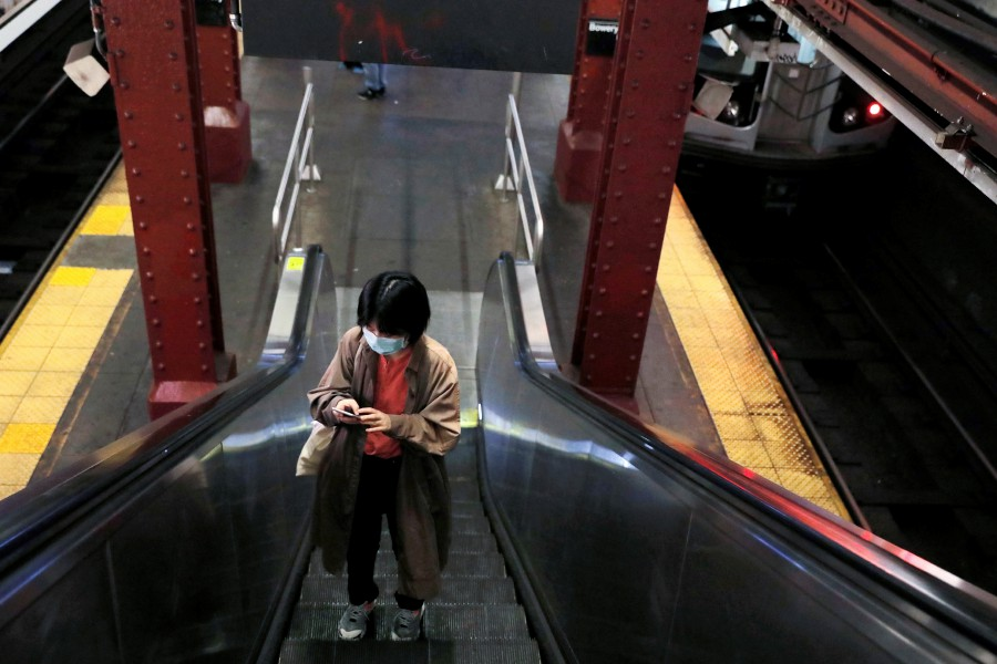 A woman in a surgical mask rides an escalator at the Bowery subway station after more cases of coronavirus were confirmed in New York City, New York. -REUTERS pic