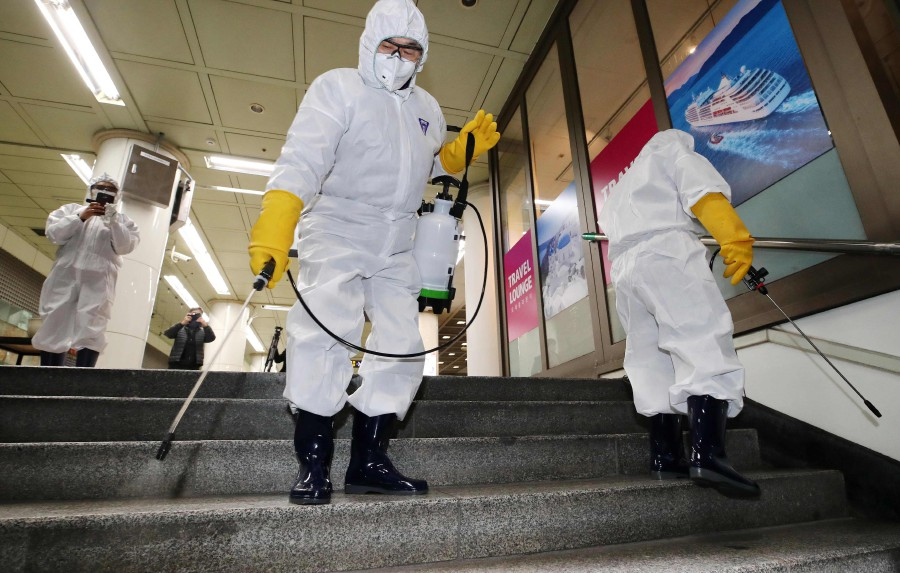 Workers wearing protective gear spray disinfectant as part of preventive measures against the spread of the COVID-19 coronavirus, at a subway station in Seoul -YONHAP/AFP