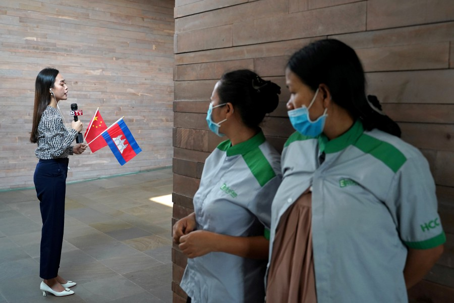 Airport cleaners in face masks observe a Cambodian TV reporter as a plane arrives from China to Cambodia with supplies and doctors donated to contain the spread of the coronavirus disease (COVID-19) outbreak, at Phnom Penh International Airport in Cambodia. -REUTERS pic