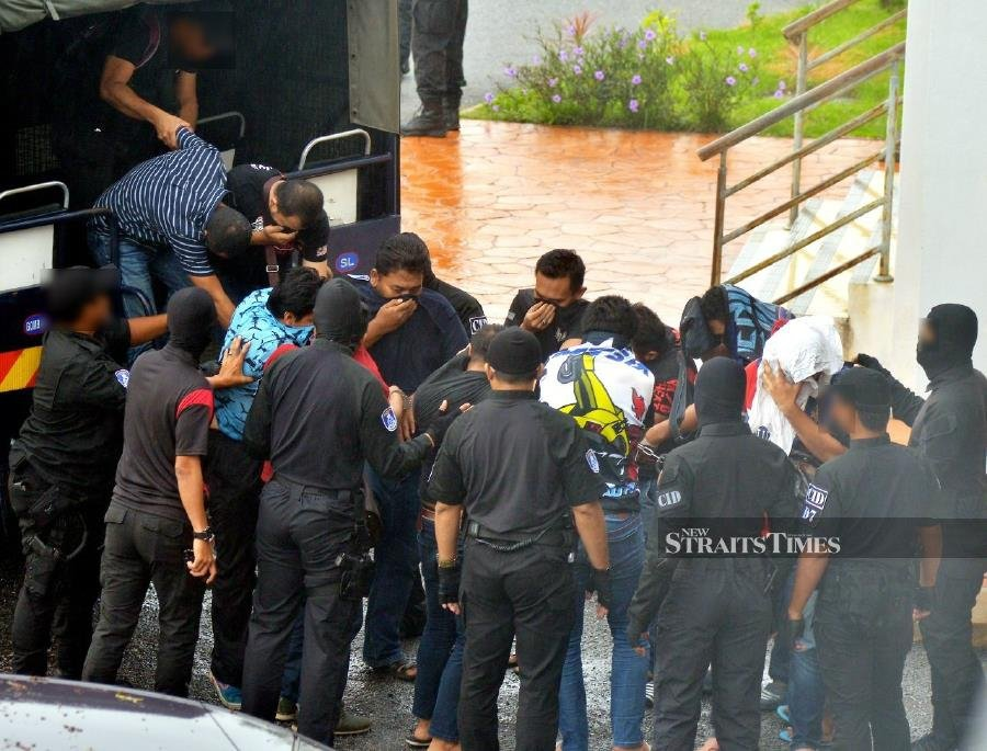 Gang leader and members of the Ayah Yie Tiger 99 group are led by policemen at the Klang Sessions Court. - NSTP/Faiz Anuar