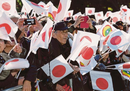 Well-wishers are waving national flags and chanting 'Banzai', a Japanese expression meaning 'ten thousand years' towards Japan's Emperor Akihito to celebrate the Emperor's 81st birthday. EPA