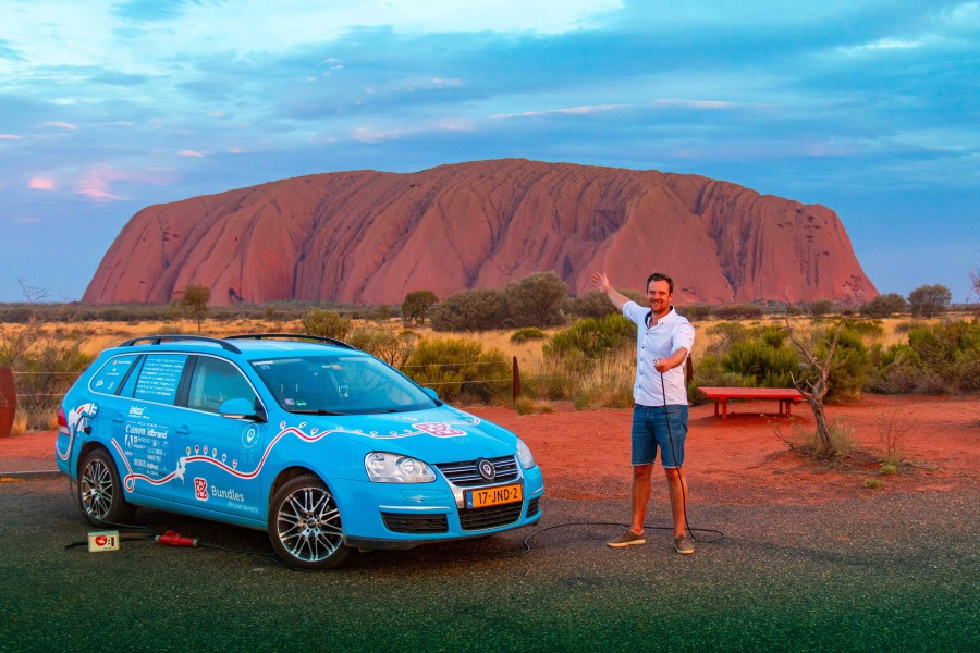 """In this handout photo taken on December 31, 2018 and released on April 7, 2019 from Dutch driver Wiebe Wakker (C-R) shows him at Uluru in the Northern Territory with his retrofitted station wagon nicknamed """"The Blue Bandit"""" during his round-the-world trip in the electric car. - Wakker arrived in Sydney on April 7, 2019 after driving some 95,000 kilometres (59,000 miles) across 33 countries in what he said was the world's longest-ever journey by electric car. AFP"""