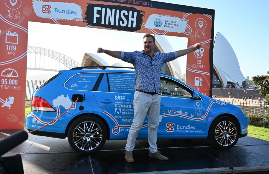 """Dutch driver Wiebe Wakker (C) celebrates after driving his retrofitted station wagon nicknamed """"The Blue Bandit"""" onto a platform to complete a round-the-world trip in the electric car with a backdrop of Sydney Harbour Bridge in Sydney on April 7, 2019. - Wakker drove some 95,000 kilometres (59,000 miles) across 33 countries in what he said was the world's longest-ever journey by electric car. AFP"""