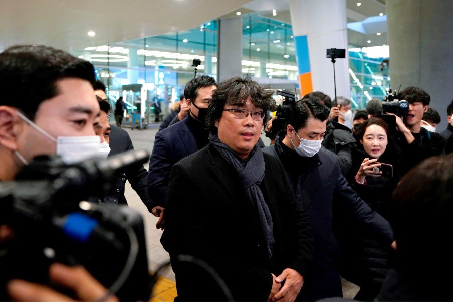 Director of four Oscar award-winning film 'Parasite' Bong Joon-ho is escorted by security personnel as he leaves Incheon International Airport, South Korea. (REUTERS)