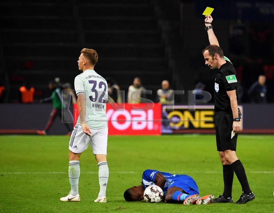 Bayern Munich's Joshua Kimmich (left) is booked by referee Marco Fritz (right) during the German Bundesliga match in Berlin, Germany. - EPA