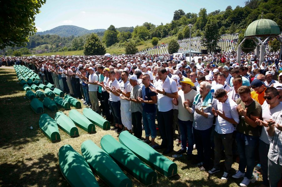 People pray near coffins of their relatives, who are newly identified victims of the 1995 Srebrenica massacre, which are lined up for a joint burial in ...