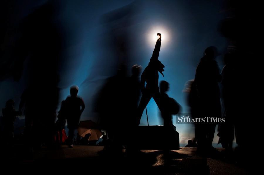 FILE PHOTO: People walk around a statue of singer Freddie Mercury along the lakeside during the 45th Montreux Jazz Festival in Montreux July 2, 2011. Over 350 artists and groups will perform on the two main stages and at the ten free venues during the sixteen-day long festival. REUTERS Photo