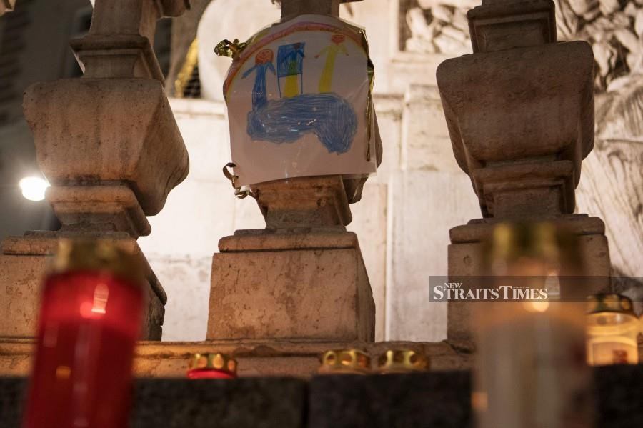 A child's drawing is fixed at the plague column (Trinity Column) in Vienna's city centre. People placed candles as a sign of hope against the corona virus on the pillar in Vienna. The plague column (Trinity Column) was built after the great plague epidemic in 1679. Photo by ALEX HALADA/AFP