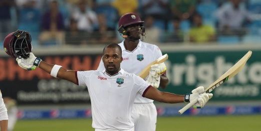 West Indies batsman Darren Bravo (front) raises his bat and helmet as he celebrates after scoring century (100 runs) as team captain Jason Holder looks on the final day of the first day-night Test against Pakistan at the Dubai International Cricket Stadium. AFP