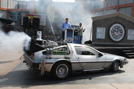 """(FILES)-- A file photo taken on August 2, 2007 shows US actor Christopher Lloyd (passenger's seat) arriving in a """"Back to the Future"""" style DeLorean at a ceremony to mark a month-long countdown to the closure of the 14-year-old """"Back to the Future - The Ride"""" at Universal Studios Hollywood in University City, California. When Marty McFly and """"Doc"""" Brown burst into 2015 in a time machine, straight from the year 1985, they encounter a brave new world of garbage-fueled flying cars, self-tying shoes and robot waiters. AFP PHOTO"""