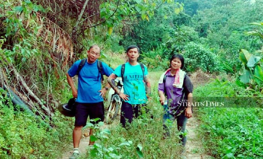 SK Buayan teachers,(from left) Tay Oi Leng, Jeffery Joseph and Zeabenia Mositol walked for 12km to a Year 4 pupil's house to persuade the child to return to school after being absent for three weeks. NSTP/PICS COURTESY OF SK BUAYAN