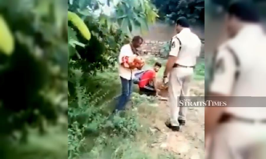 This videograb from a social media video shows a policeman questioning the to two men as they were about to bury the newborn baby girl in Hyderabad, India.