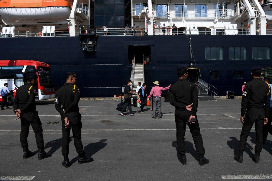 Cambodian military police officials stand guard as passengers disembark from the Westerdam cruise ship in Sihanoukville. - AFP