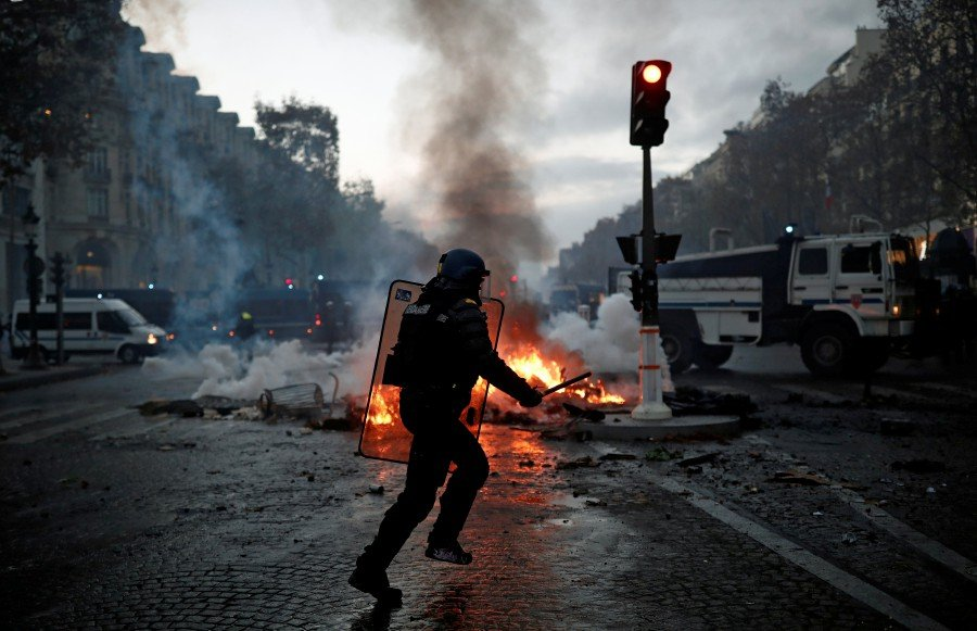 clashes on champs elysees as french protesters rage against taxes