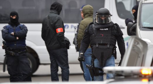 Security forces personnel walk past during ongoing operations in the Molenbeek district of Brussels on November 16, 2015. Belgian police launched a major new operation in the Brussels district of Molenbeek, where several suspects in the Paris attacks had previously lived, AFP journalists said. Armed police stood in front of a police van blocking a street in the run-down area of the capital while Belgian media said officers had surrounded a house. Belgian prosecutors had no immediate comment.AFP Photo