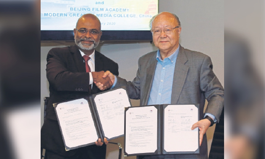 Professor Dr Pradeep Nair and Professor Dr Wang Chenglian exchanging documents after signing a memorandum of understanding at Taylor's University Lakeside Campus on Jan 7.