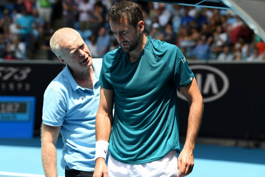 Croatia's Marin Cilic receives medical treatment during his men's singles match against Canada's Milos Raonic on day seven of the Australian Open tennis tournament in Melbourne. -AFP