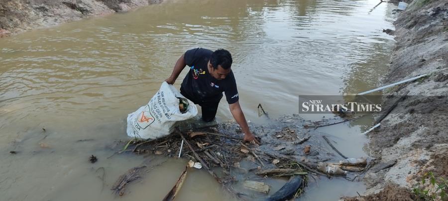 SK FELDA Besout 1 teacher Ismail Mohd Zain collecting rubbish at Sungai Balun in Slim River, Tanjung Malim. - NSTP/ROSMAN SHAMSUDIN.