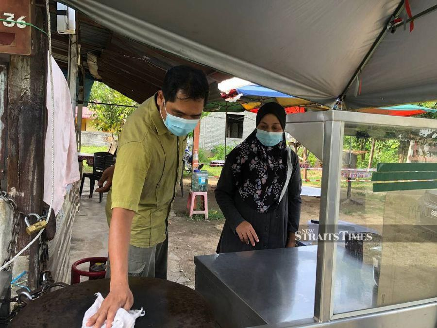Mohd Azizi (left), who sells colek at night during the fasting month in front of his house, was slapped with a RM50,000 fine for flouting the MCO and operating beyond the 10pm limit on April 26. - NSTP / NOR FAZLINA ABDUL RAHIM.
