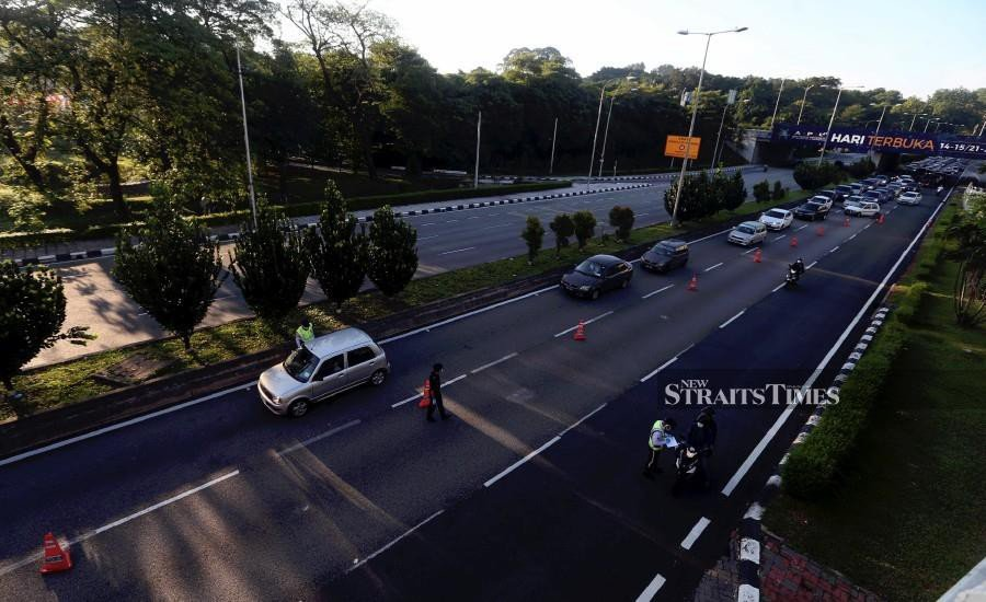 Police officers manning a roadblock in Kuala Lumpur this morning amid the Movement Control Order. - NSTP/HAIRUL ANUAR RAHIM